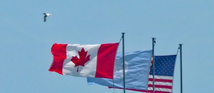 The Canadian flag flies next to an American flag, separated by the UN's flag. Refugee lawyers and refugee law advocates are likely still celebrating the funding laid out for immigration programs by Canada's 2018 federal budget.