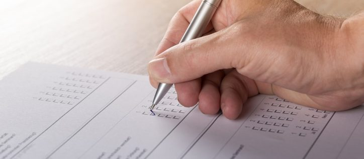A hand holding a pen filling out a survey, similar to the one about immigration in Canada.