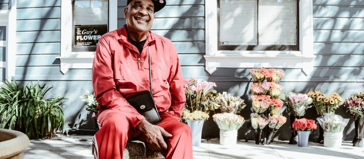 An aging man sitting outside a flower shop wearing a tracksuit and a ball cap.