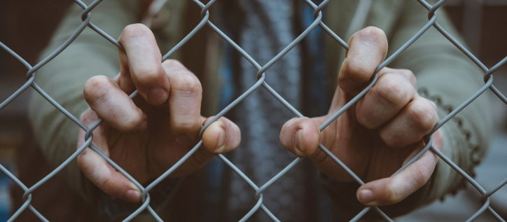 A man in a gray jacket clutches a chain-link fence in front of him.