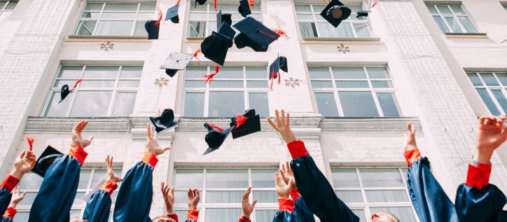 Graduates throw their mortarboards into the air as they celebrate outside their university.