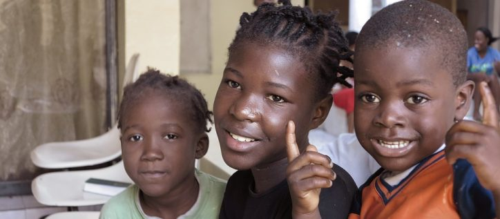 Three young African children smile as they wait in a detention centre.