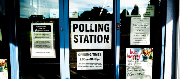 A sign for a polling station sits in a glass door.