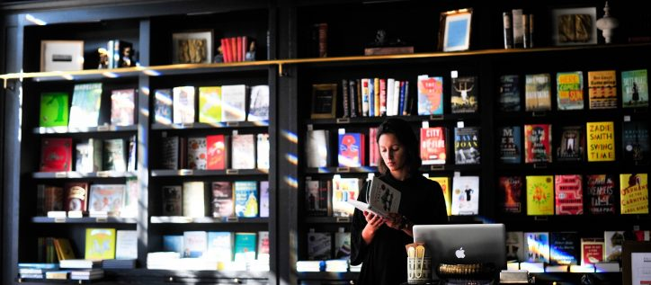Business woman reads behind the counter of her manicured book shop.