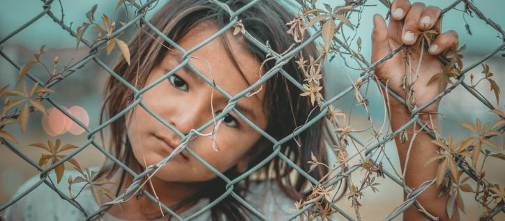 Sad black-haired girl stands behind an overgrown fence.