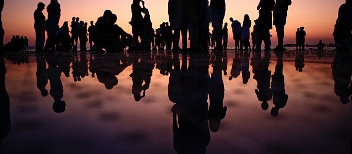 Shiloutte of a crowd gathered together in the sunset with their shadows reflected on the ground.