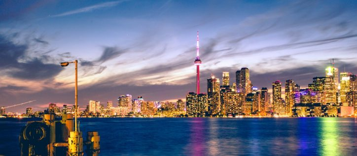 A sunset view of a brightly-lit Toronto, a city in Ontario facing particular challenges when helping asylum seekers.