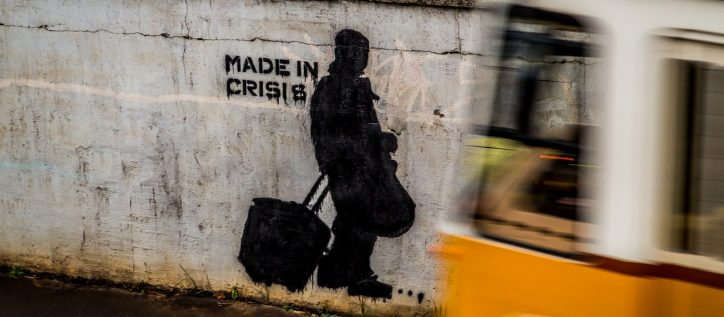 Made in crisis is graffitied on a cement wall.
