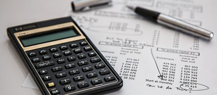 "A calculator sits on top of a sheet of investment sums, with the words ""Can we do this?"" written in black ink on it."