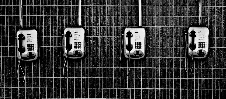 Four black and white public phones hang on a tiled wall.