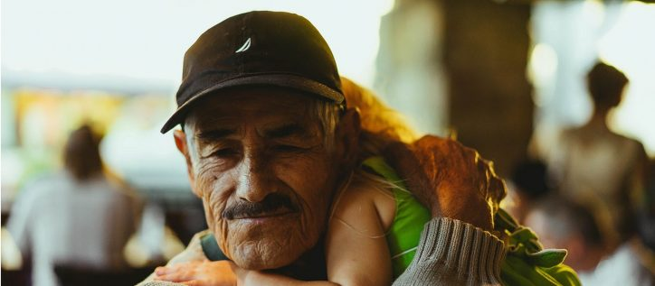 Old man looks relieved as he holds his grandchild