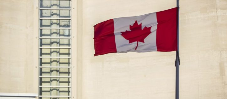 A Canadian flag waves in front of a beige concrete building wall.