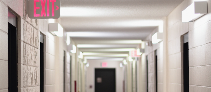 Corridor of student dorm with an illuminated Exit sign