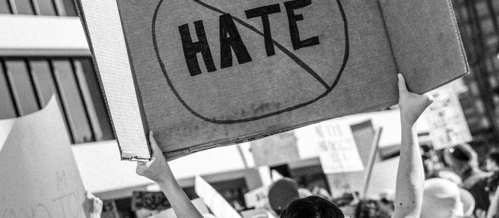 Woman at a protest holds a no hate sign