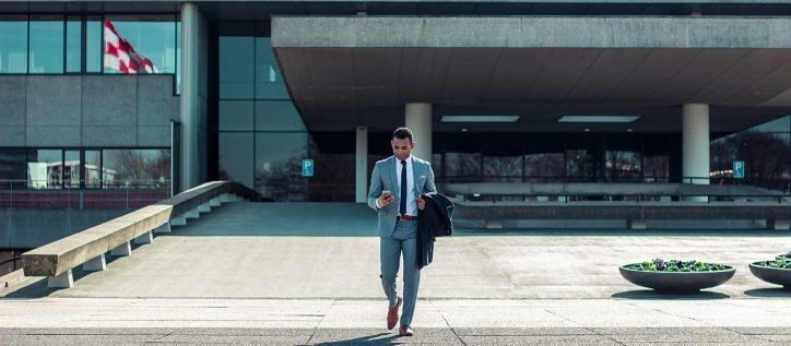 Man walking out of federal government building in Canada wearing a grey suit