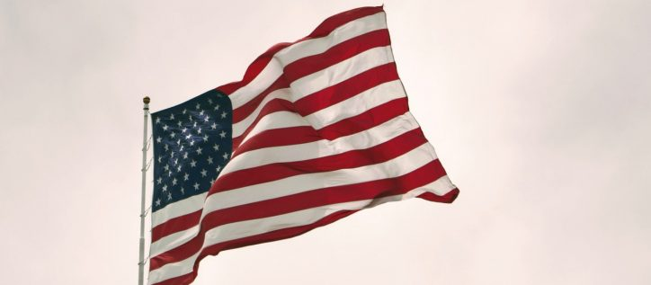 An American flag atop a flagpole waves in the wind.