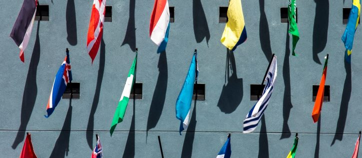 International flags hanging on a stone wall outside
