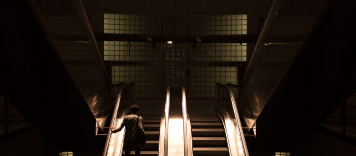 man stands on an escalator in a dimly lit foyer
