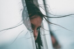 Young girl looks out of the window of a moving vehicle