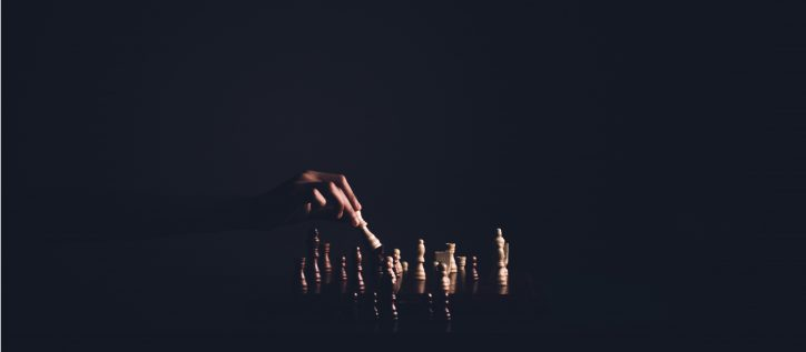 hand moves a chess piece in a dark room