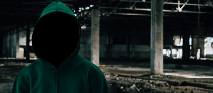 A mysterious hooded figure stands in front of an abandoned underpass