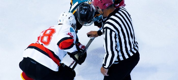 Hockey players face off on the ice as a referee prepares to drop the puck.