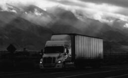 A semi truck drives on a gloomy road.