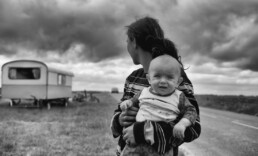 Woman holds her baby on the side of a highway with a trailer in the background