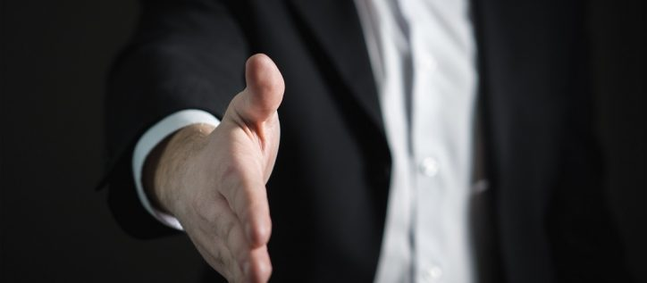 Man in a black suit puts hand out for handshake