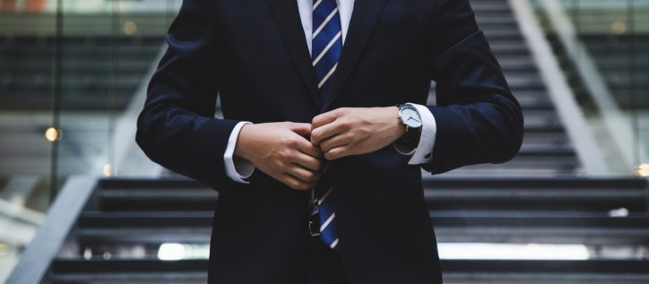 A man buttoning up his suit.