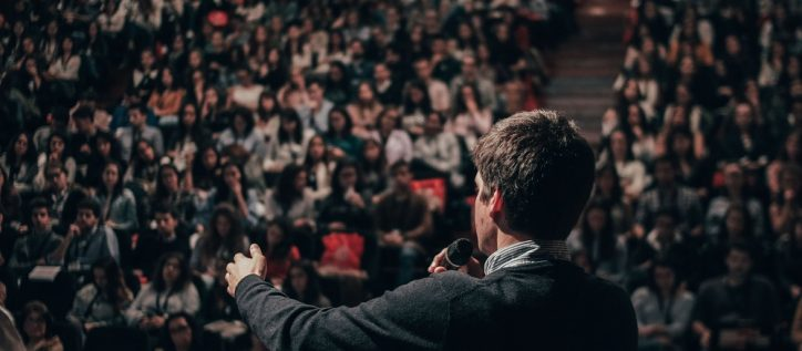 Man gives a speech in front of a large auditorium filled with people