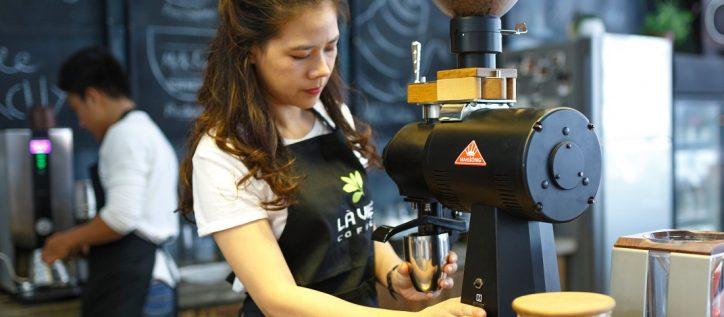 Female cafe worker makes a beverage