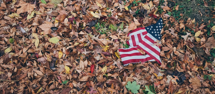 American flag on the ground covered in dead leaves