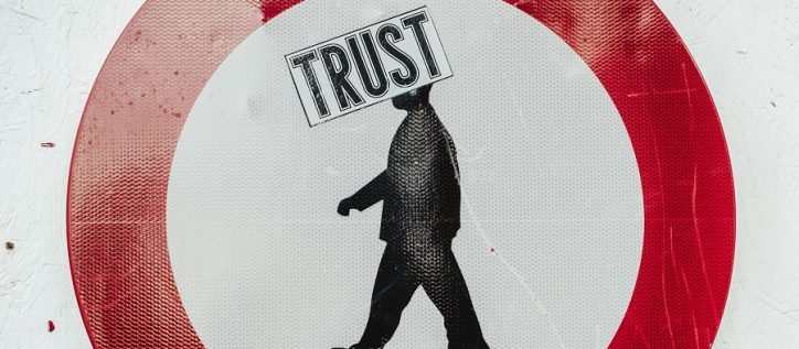 "Red sign with man inside with the word ""trust"" over his face"