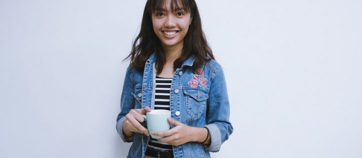 Woman with brown hair wearing a jean jacket holds a cup of coffee smiles