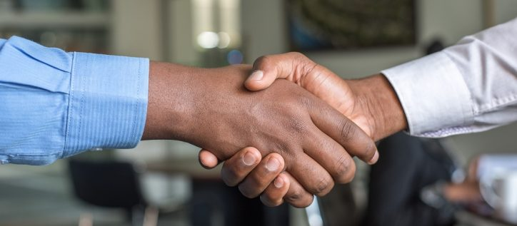 Two men shake hands in a business setting