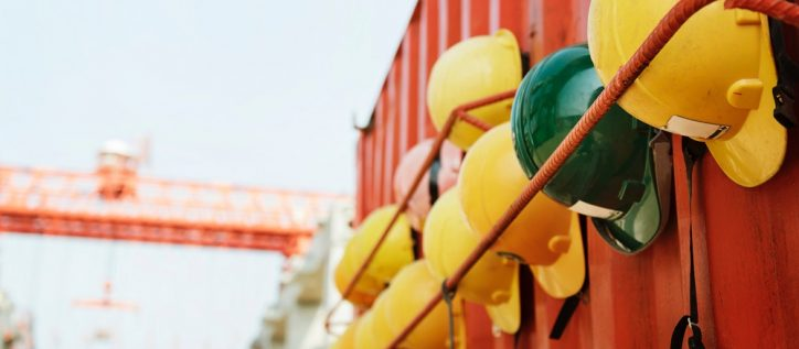 yellow and green hardhats lined up along a metal container