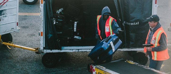 two men working at an airport loading luggage onto the plane