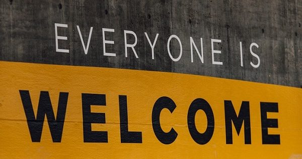 'Everyone is Welcome' Painted on concrete wall surrounded by graffiti