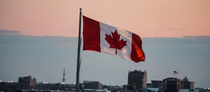 Canadian flag flying over city skyline