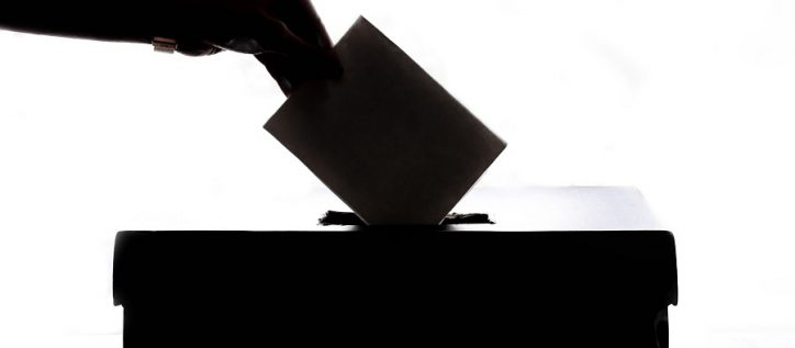 Person drops ballot into ballot box