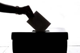 Person drops ballot into ballot box