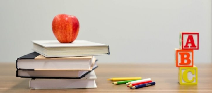 Desk with school books and apple