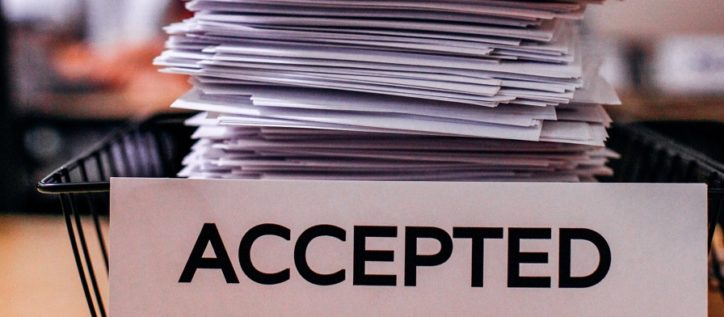 Stack of papers in basket with 'Accepted' Sign