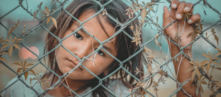 Refugee child behind chain link fence