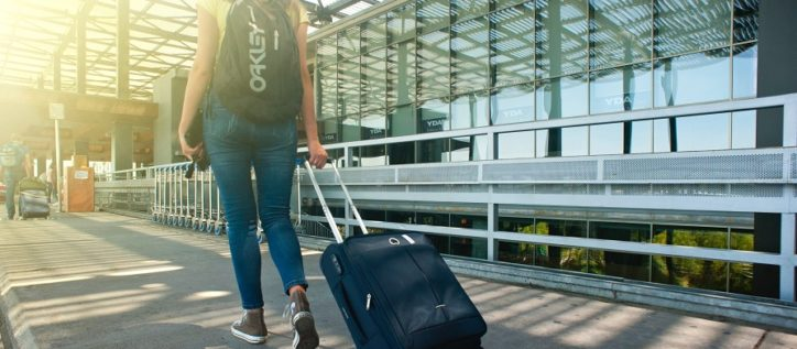Woman at airport pulling suitcase