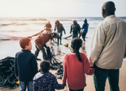 Refugees standing on the beach