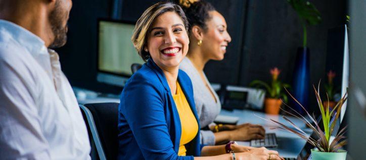 smiling woman sitting at computer