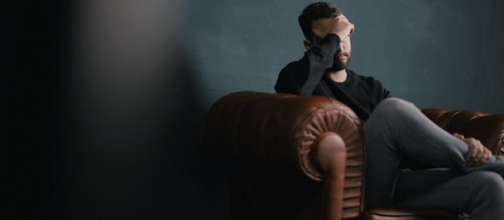 Man sitting on couch with hand covering his face