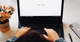 Hands typing search into Google on laptop